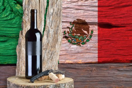 bottle of wine with Mexico flag in the background